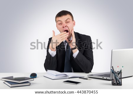 Businessman in office yawning over gray background