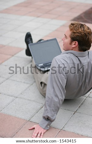 Businessman in relaxed position sits in the middle of the plaza with his laptop on his lap