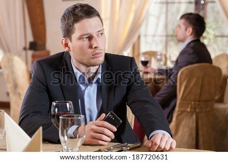 Businessman in restaurant waiting for his partner