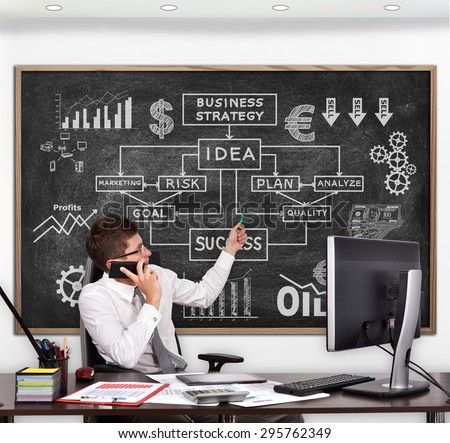 businessman in room pointing to blackboard with drawing business concept - stock photo