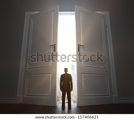 businessman in room with big door to city - stock photo