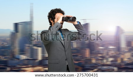 Businessman in search for opportunities on the top of a skyscraper - stock photo