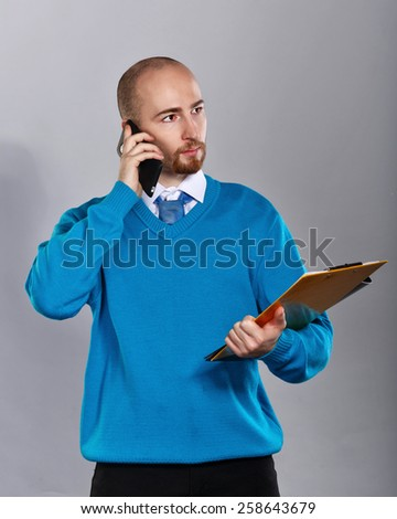 Businessman in shirt and tie talking on cell phone and holding a folder with papers. Business people. Concept of success. - stock photo