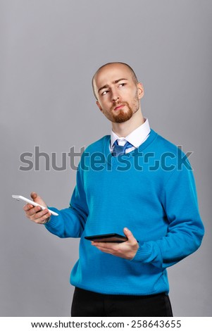 Businessman in shirt and tie talking on cell phone and holding a tablet PC. Business people. Concept of success. - stock photo