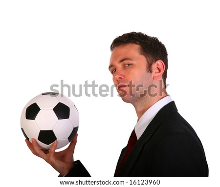 Businessman in side pose holding traditional colored soccer ball