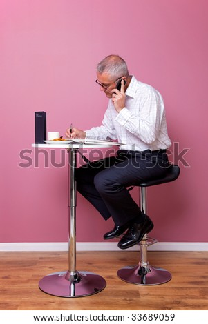 Businessman in smart casual attire sat on a bar stool in a cafe working through his lunch break. - stock photo