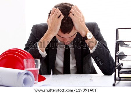 Businessman in stress holding his head with hands sitting at the table - stock photo