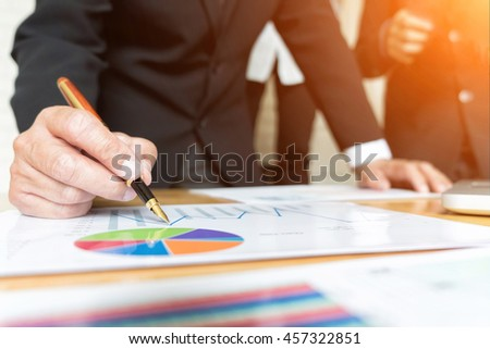 businessman in suit analyzing investment charts with pen, Accounting and Business concept, soft focus, vintage tone - stock photo