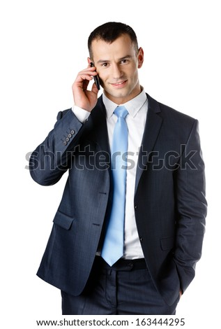 Businessman in suit and blue tie talking on phone, isolated on white - stock photo