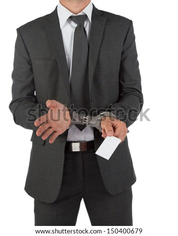 Businessman in suit and handcuffs handing over a blank business card isolated on white
