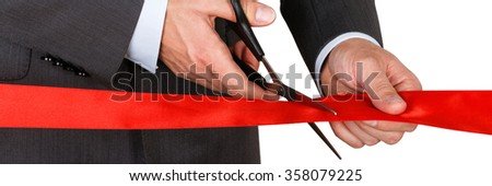 Businessman in suit cutting red ribbon with pair of scissors isolated on white background. Grand opening concept. Traditional public festive ceremony. Letter box format - stock photo