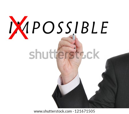 Businessman in suit drawing text of the word impossible with red mark through part of the word making it now possible - stock photo