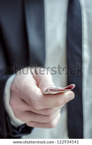 Businessman in suit giving ten Euro banknotes.