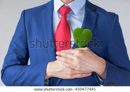 Businessman in suit holding a green heart shape - white background - indicates ecofriendly , social and environmental responsiblility business concept - stock photo