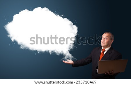 Businessman in suit holding a laptop and presenting abstract cloud copy space - stock photo