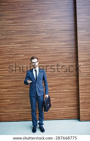 Businessman in suit holding briefcase and cellphone - stock photo