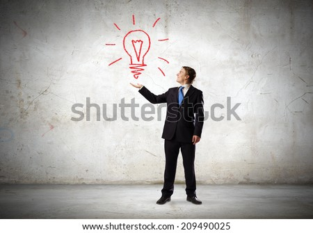 Businessman in suit holding light bulb in palm