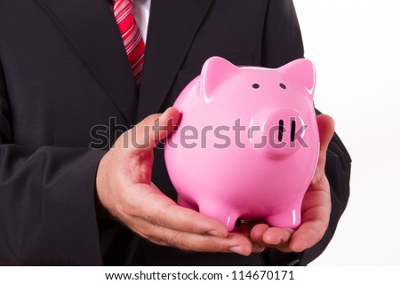 Businessman in suit holding pink piggy bank with both hands, isolated on white background.