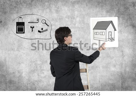 businessman in suit holding poster with real estate symbol
