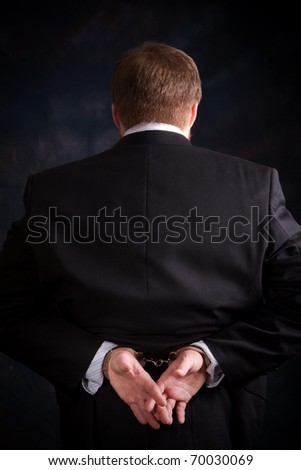 Businessman in suit is handcuffed behind his back. - stock photo