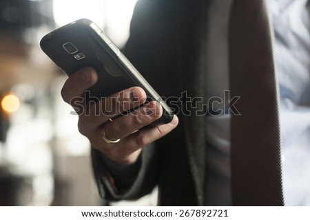 Businessman in suit, jacket,shirt, tie, using his smart phone - stock photo