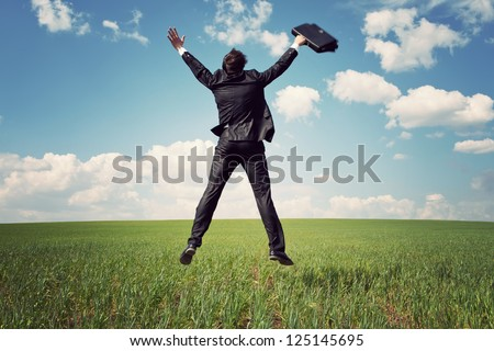 businessman in suit jumping in field and holding the bag - stock photo