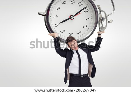 Businessman in suit lifting up something heavy against grey background