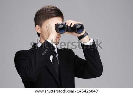 Businessman in suit looking through a binoculars with gray  background - stock photo