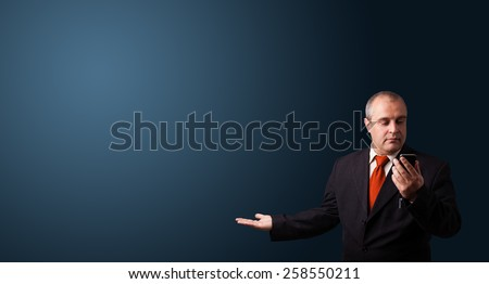 businessman in suit making phone call and presenting copy space - stock photo