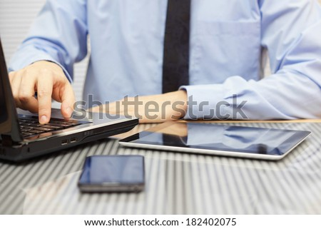 businessman in suit on office typing on laptop and watching  tablet - stock photo