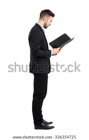 Businessman in suit reading document or contract side view. Full body length portrait isolated over white studio background.  - stock photo