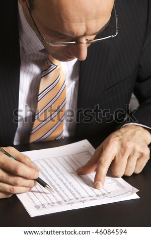 Businessman in suit sitting at desk in office working on a table - stock photo