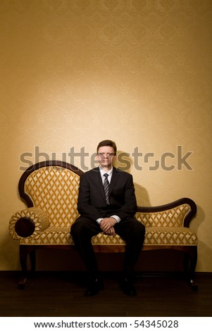 businessman in suit sitting on sofa in room, combined hands together - stock photo