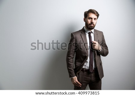 Businessman in suit standing against light wall. Mock up