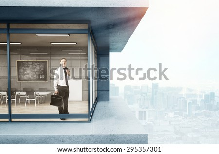 businessman in suit standing in loft office - stock photo