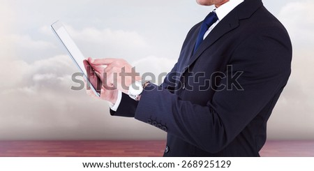 Businessman in suit using digital tablet against clouds in a room - stock photo