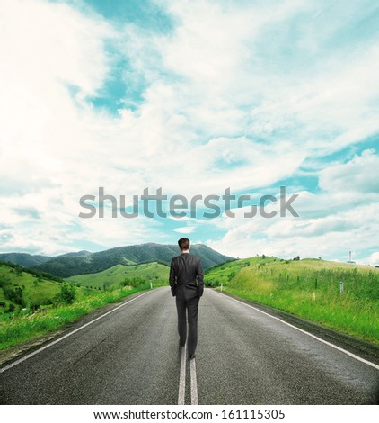 businessman in suit walking on road - stock photo