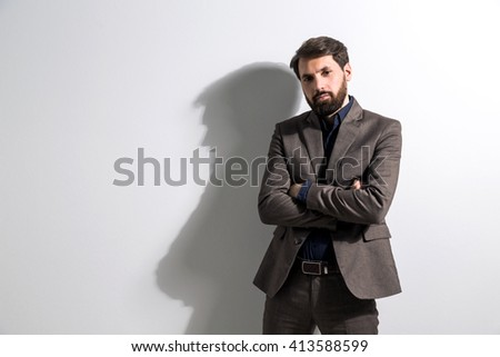 Businessman in suit with crossed arms standing against white wall. Mock up