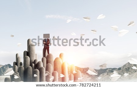 Businessman in suit with laptop instead of head keeping arms crossed while standing on the top of stone column among flying paper planes with beautiful skyscape on background. 3D rendering.