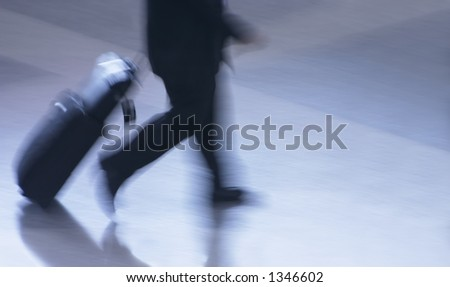 Businessman in suit with luggage walking hurriedly to catching his flight - stock photo