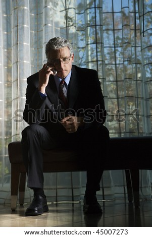 Businessman in suit with serious expression sitting talking on a mobile phone. Vertical shot. - stock photo