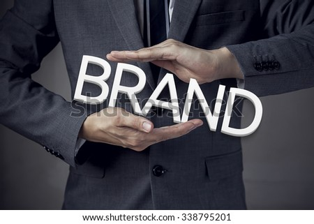 """Businessman in suit with two hands in position to protect the word """"BRAND"""" (focus on hand, blur out the suit). - stock photo"""