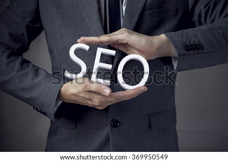 """Businessman in suit with two hands in position to protect the word """"SEO"""" (focus on hand, blur out the suit). - stock photo"""