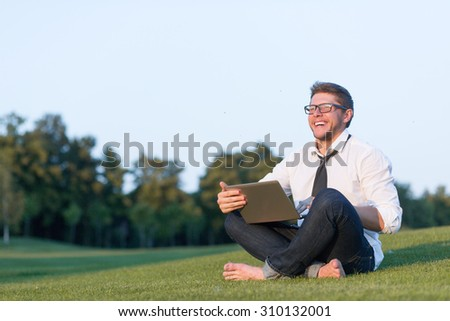 Businessman in summer park working in green environment. Man in glasses and casual clothes smiling and looking away. - stock photo