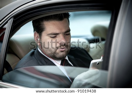 Businessman in taxi listening to music on his phone