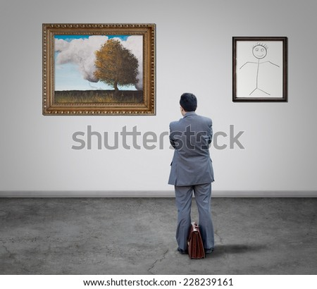 Businessman in the art gallery looking paintings  - stock photo