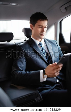Businessman in the car with the tablet - stock photo
