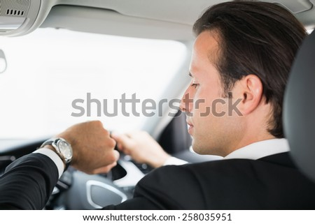 Businessman in the drivers seat in his car - stock photo
