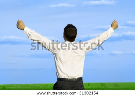 businessman in the meadow with dark blue sky - stock photo