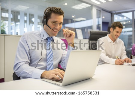 Businessman in the office on the phone with headset, Skype,FaceTime - stock photo